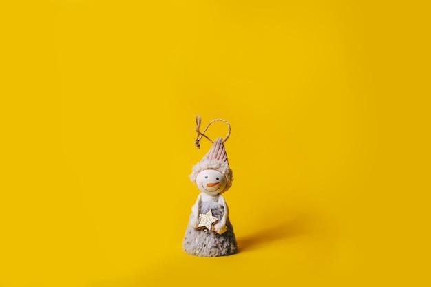 Маленькая снежная игрушка на желтом фоне