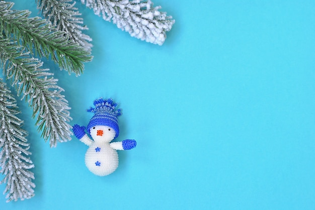 Little snowman christmas decoration toy in blue hat waiving near the cristmas tree branch with copy space