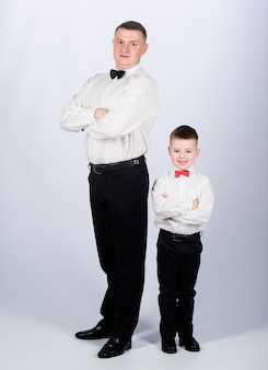 Little son following fathers example of noble man. gentleman upbringing. father and son formal clothes outfit. grow up gentleman. dad and boy white shirts with bow ties. gentleman upbringing.