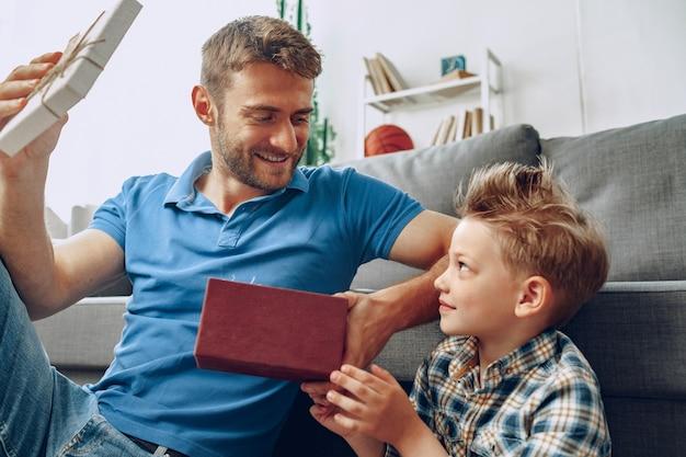 Маленький сын дарит отцу подарочную коробку на день отца