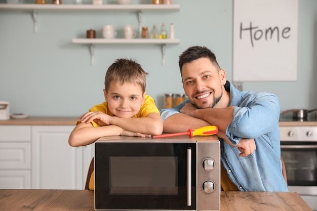 Little son helping his father to repair microwave oven in kitchen