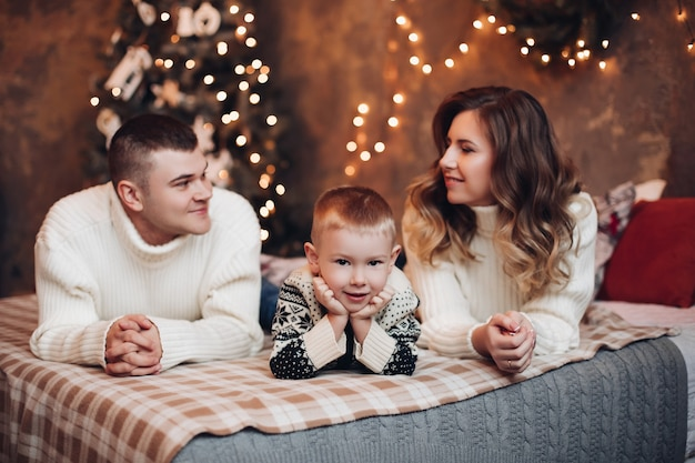 Little son and his parents lying on the bed with the christmas tree