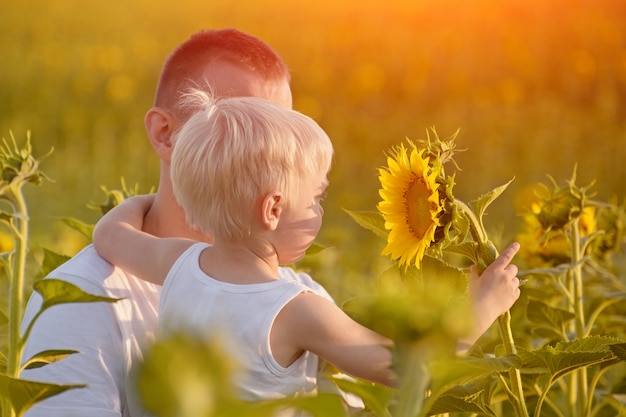 Little son holds a flower sunflower sitting on hands of the father