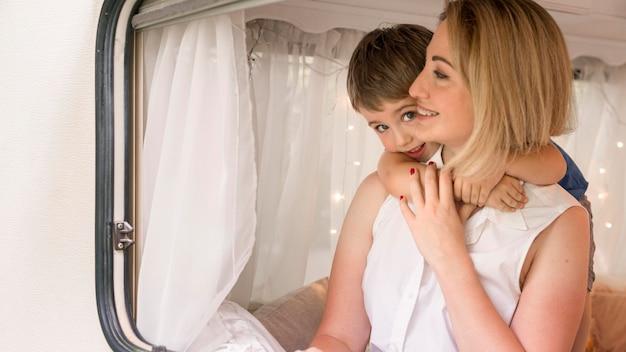 Little son hugging his mother in caravan