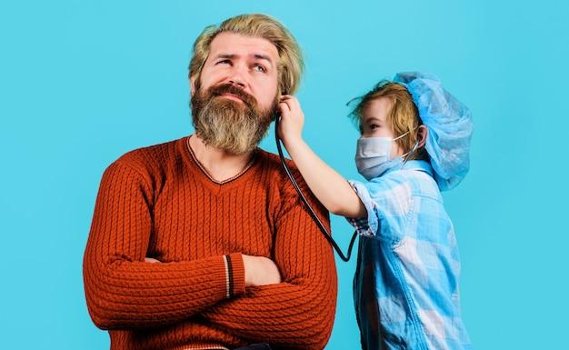 의료용 마스크를 쓴 작은 아들은 아빠와 의사로 게임을 합니다. 귀여운 아이 소년 청진 기 아버지 환자를 듣고 의사 척.