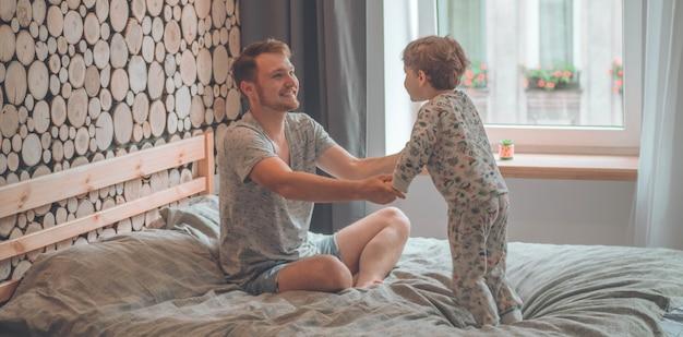 Маленький сын играет с отцом на диване. счастливая любящая семья