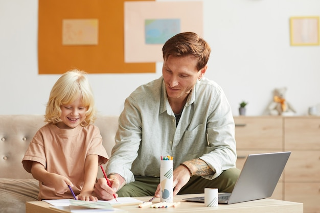 テーブルに座って、家でカラフルな鉛筆で父親と一緒に絵を描く幼い息子