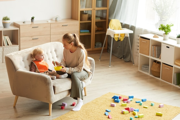 Little son sitting on sofa while his mother giving him the porridge for lunch after leisure games