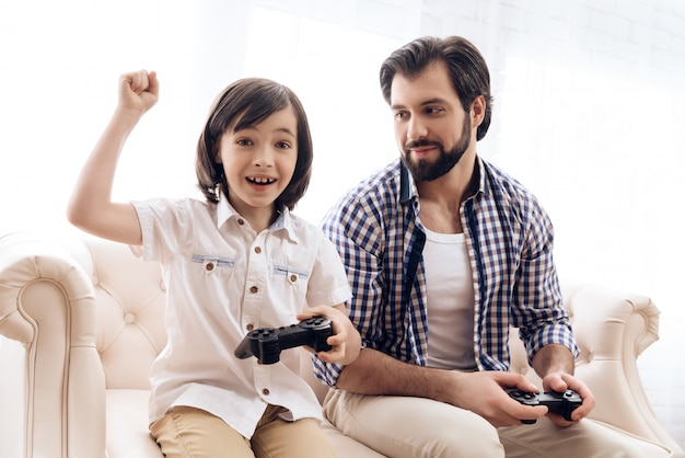 Little son with joystick rejoice at victory in game with father.