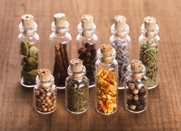 Маленькие сувенирные бутылки со специями над деревянным столом