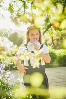 花に囲まれたロリポップを噛んで立っている小さなスペインの女の子