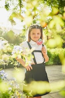 小さなスペインの女の子は、カメラに微笑んで花で囲まれたロリーポップで立っています