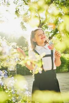 小さなスペインの女の子は花で囲まれた目をまばたきロリーポップで立っています