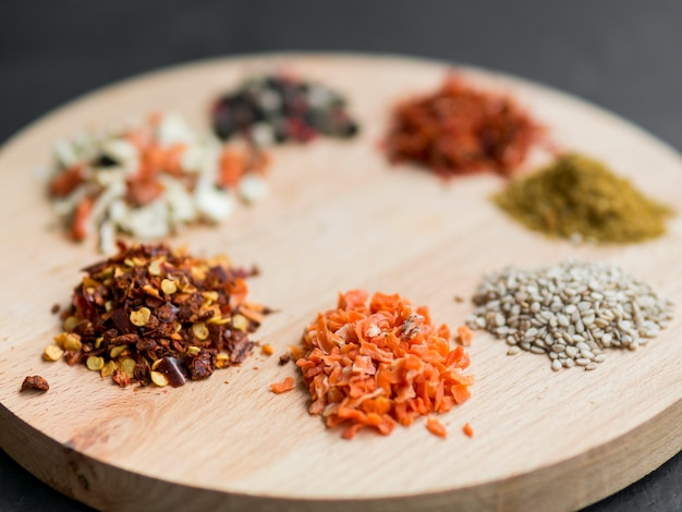 Little spice piles on wooden tray