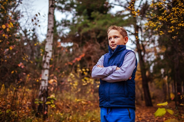 Little sportive boy having rest after exercises in the forest