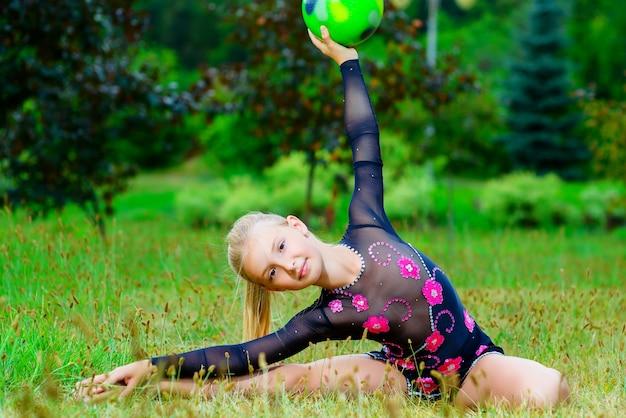 Маленькая спортивная девочка тренируется в парке