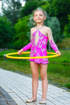 Маленькая спортивная девочка тренируется с обручем