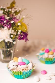 Little stones in baskets near vase with flower bouquet