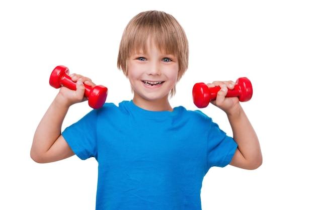 少し強い男。カメラを見て、ダンベルで運動し、白で隔離されて立っている間笑顔の陽気な男の子