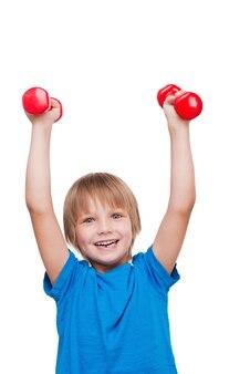 少し強い男。カメラを見て、ダンベルで運動し、白で隔離されて立っている間笑顔で幸せな小さな男の子