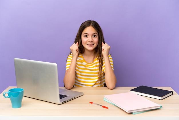 Маленькая девочка-студент на рабочем месте с ноутбуком, изолированным на фиолетовом фоне, празднует победу в позиции победителя