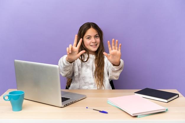 Маленькая девочка-студент на рабочем месте с ноутбуком, изолированным на фиолетовом фоне, считая восемь пальцами