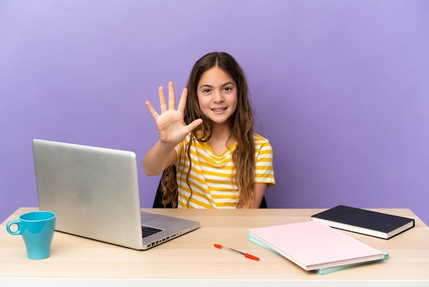Маленькая девочка-студент на рабочем месте с ноутбуком, изолированным на фиолетовом фоне, считая пять пальцами