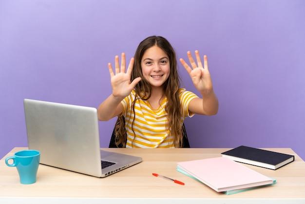 Маленькая девочка-студент на рабочем месте с ноутбуком, изолированным на фиолетовом фоне, считая девять пальцами