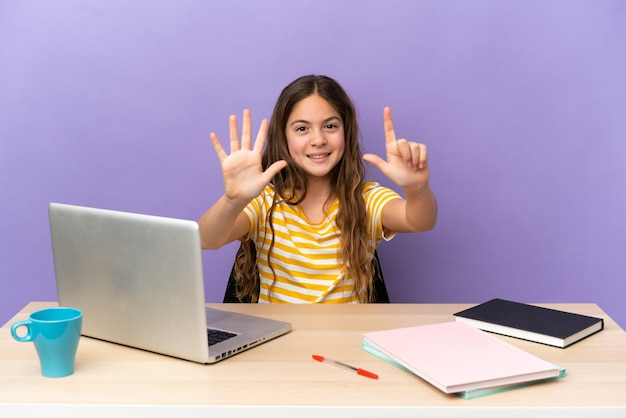 Маленькая студентка на рабочем месте с ноутбуком, изолированным на фиолетовом фоне, считая семь пальцами