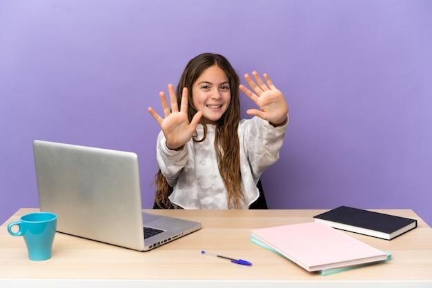 Маленькая студентка на рабочем месте с ноутбуком, изолированным на фиолетовом фоне, считая десять пальцами