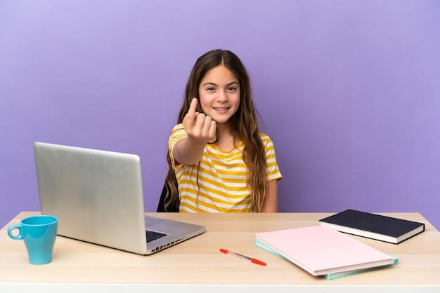 Маленькая студентка на рабочем месте с ноутбуком, изолированным на фиолетовом фоне, делает приближающийся жест