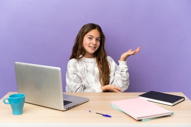Маленькая студентка на рабочем месте с ноутбуком, изолированным на фиолетовом фоне, протягивая руки в сторону, приглашая приехать