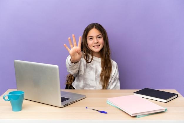 Маленькая студентка на рабочем месте с ноутбуком, изолированным на фиолетовом фоне, счастлива и считает четыре пальцами