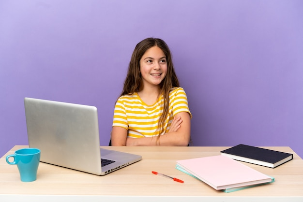 Маленькая студентка на рабочем месте с ноутбуком, изолированным на фиолетовом фоне, счастлива и улыбается
