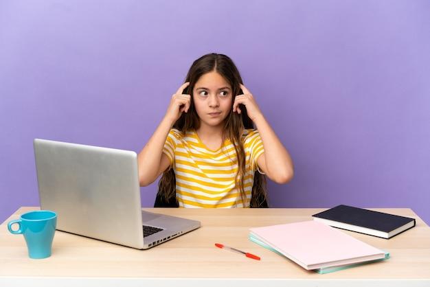 Маленькая девочка студента на рабочем месте с ноутбуком, изолированным на фиолетовом фоне, сомневаясь и думая