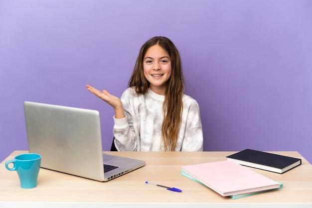 Маленькая студентка на рабочем месте с ноутбуком, изолированным на фиолетовом фоне, держа воображаемое copyspace на ладони, чтобы вставить рекламу