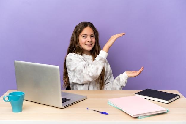 Маленькая студентка на рабочем месте с ноутбуком, изолированным на фиолетовом фоне, держит copyspace для вставки рекламы