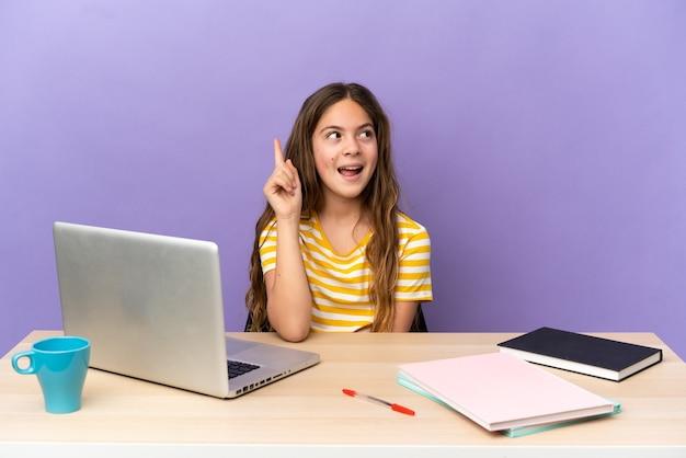 Маленькая студентка на рабочем месте с ноутбуком, изолированным на фиолетовом фоне, намереваясь реализовать решение, подняв палец вверх