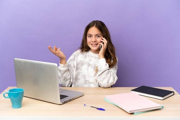 Маленькая студентка на рабочем месте с ноутбуком, изолированным на фиолетовом фоне, разговаривает с кем-то по мобильному телефону