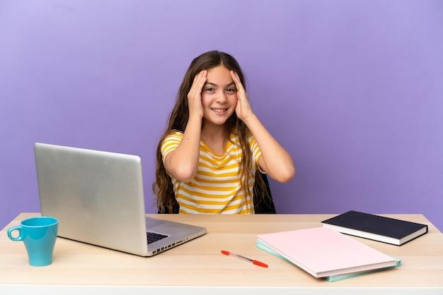 Маленькая девочка студента на рабочем месте с ноутбуком, изолированные на фиолетовом фоне смеясь