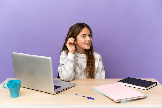 紫色の背景に分離されたラップトップを耳に手を置いて何かを聞いている職場の小さな学生の女の子