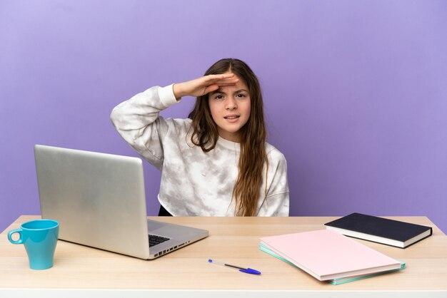 Маленькая студентка на рабочем месте с ноутбуком, изолированным на фиолетовом фоне, глядя вдаль рукой, чтобы что-то посмотреть