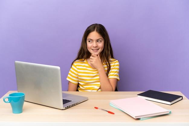 Маленькая девочка-студент на рабочем месте с ноутбуком, изолированным на фиолетовом фоне, глядя в сторону и улыбаясь