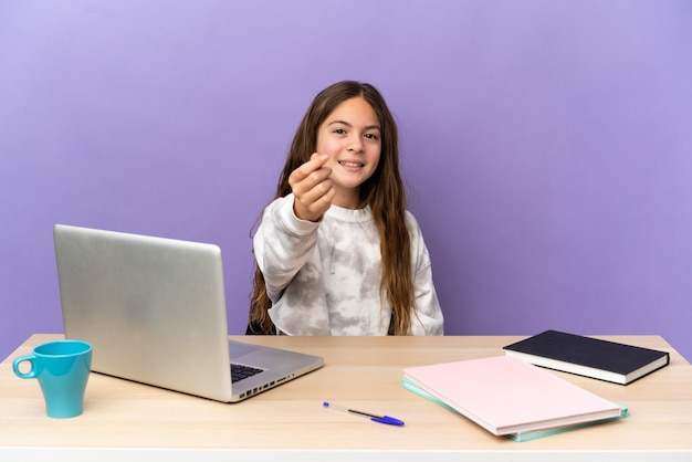 Маленькая студентка на рабочем месте с ноутбуком, изолированным на фиолетовом фоне, делая денежный жест