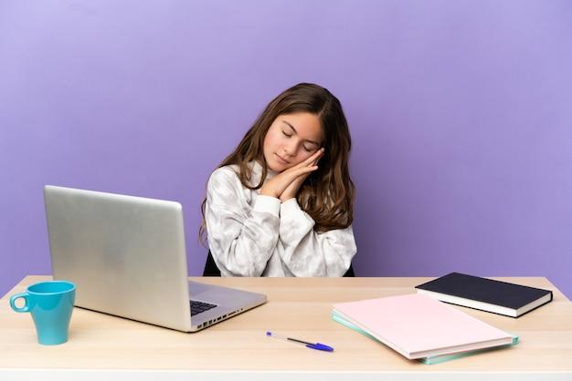 Маленькая студентка на рабочем месте с ноутбуком, изолированным на фиолетовом фоне, делая жест сна в благородном выражении