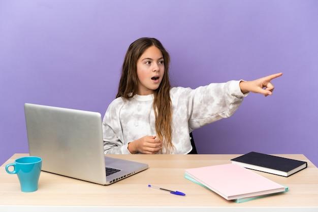 Маленькая девочка студента на рабочем месте с ноутбуком, изолированным на фиолетовом фоне, указывая в сторону