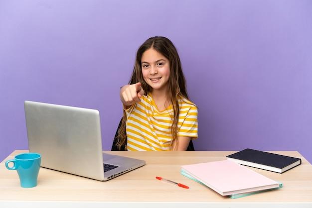 행복 한 표정으로 앞을 가리키는 보라색 배경에 고립 된 노트북과 직장에서 어린 학생 소녀