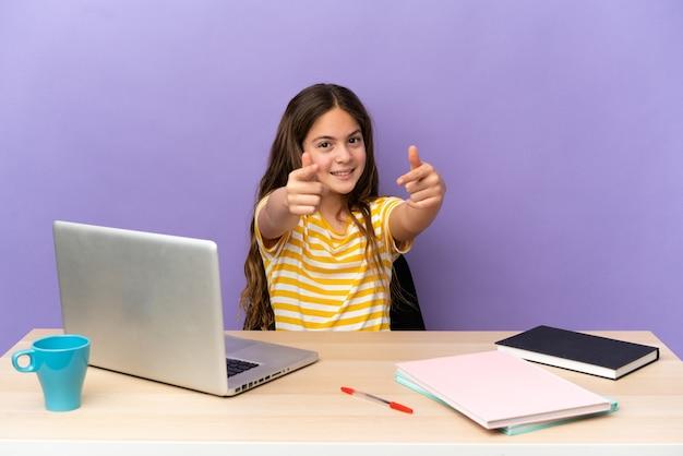 Маленькая студентка на рабочем месте с ноутбуком, изолированным на фиолетовом фоне, указывая на фронт со счастливым выражением лица