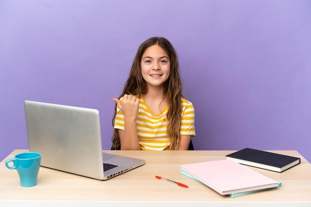 Маленькая студентка на рабочем месте с ноутбуком, изолированным на фиолетовом фоне, указывая в сторону, чтобы представить продукт
