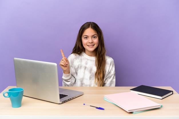 Маленькая студентка на рабочем месте с ноутбуком, изолированным на фиолетовом фоне, указывая на отличную идею